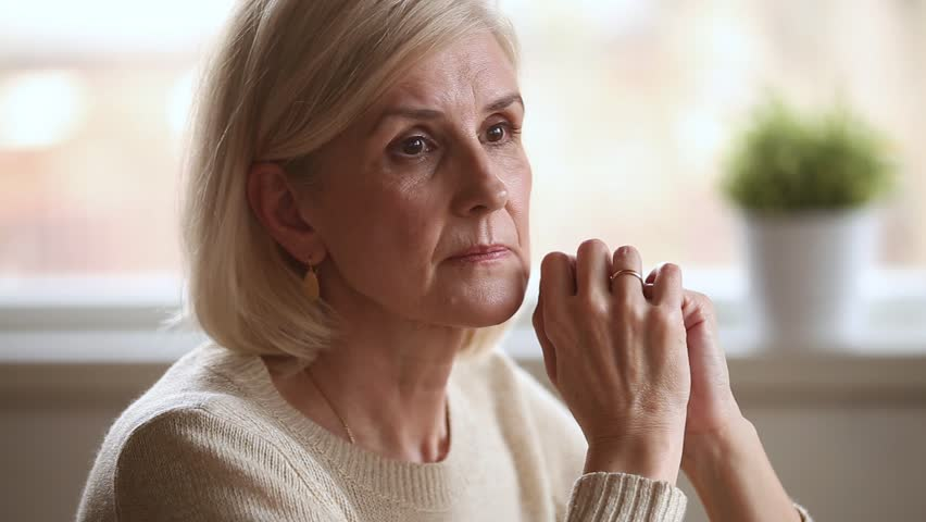Sad thoughtful anxious mature senior woman feeling lonely worried concerned about problems, pensive depressed upset middle aged widow lady sitting alone grieving thinking of getting older loneliness
