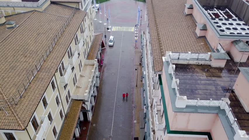 Top view of two people walking in rain. Two people go to red raincoats in rain on wet street of old town #1024154168