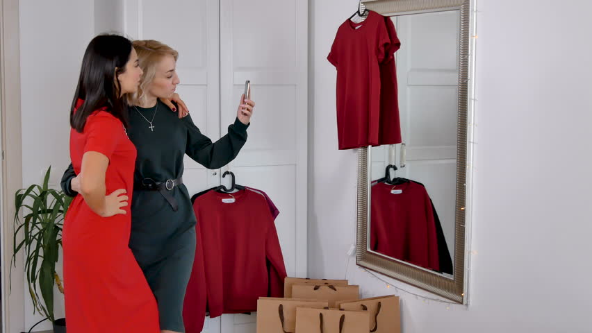 Atrractive women trying on new dress and make selfie, girls look into large mirror. Happy ladies after shopping at home try on new clothes. | Shutterstock HD Video #1024164848