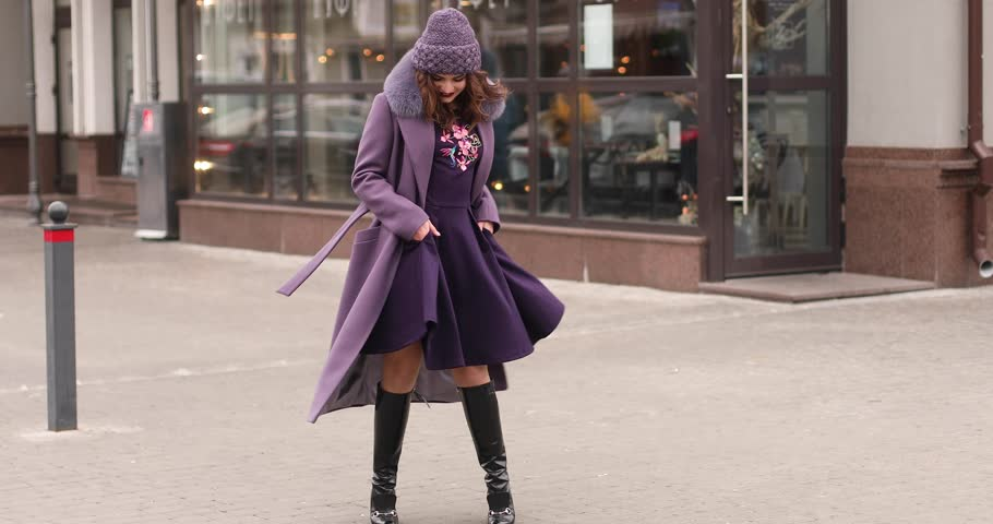 Full length footage of gorgeous fashionable lady in lilac winter hat and coat with fur collar, black high boots and deep purple dress dancing and having fun in the street of urban city. | Shutterstock HD Video #1024166858