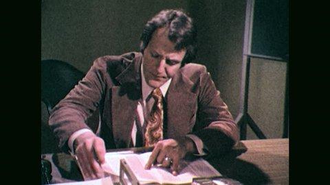 1970s: Pan to man at desk, man reading. Man opens desk drawer.