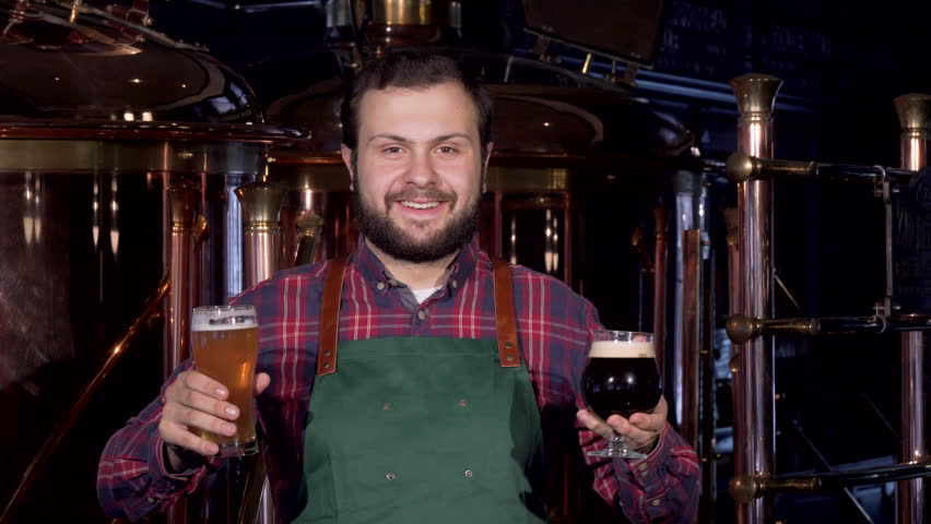 Happy male brewer in apron smiling joyfully holding two glasses of craft beer | Shutterstock HD Video #1024213448