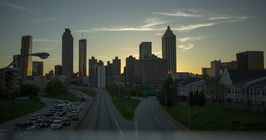 Timelapse of Atlanta Skyline from highway of sunset.  Sun goes down, lights come on.  Westin Peachtree, 191 Peachtree Tower, Promenade II, Atlanta Marriott Marquis and more in the shot.