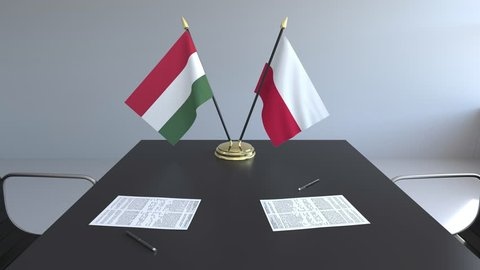 Flags of Hungary and Poland and papers on the table. Negotiations and signing an international agreement. Conceptual 3D animation