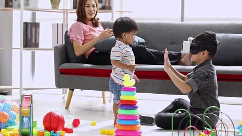 Asian mother sitting on sofa, older son use Virtual reality with his younger brother in living room, concept for family spending time together.