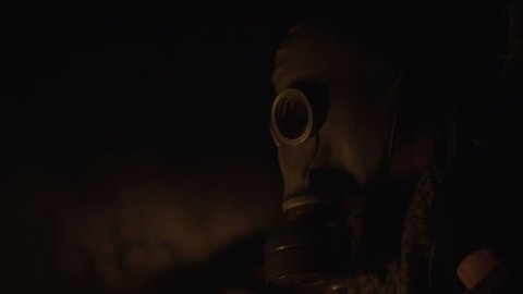 Stalker survivor Soldier Close-up Portrait wearing Gas Mask in an Apocalypse War scenario Sitting with old-style rifle near the fire