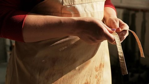 Close-up woman ceramist potter tieing apron before working with clay