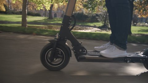Slow Motion of Modern Man Using Electric Scooter in Sunny Park 4