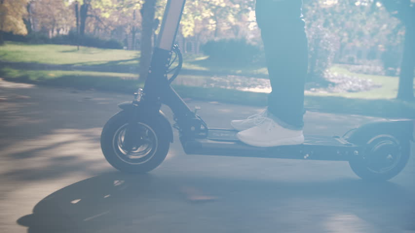 Slow Motion of Modern Man Using Electric Scooter in Sunny Park 4 | Shutterstock HD Video #1024300868