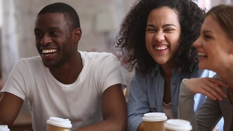 Happy multiracial young people friends talking laughing at group meeting sharing cafe table, diverse students drinking coffee having fun together enjoy multi-ethnic friendship pleasant conversation