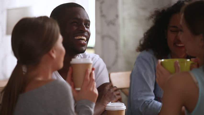 Happy african guy joking having fun laughing talking to multiracial young friends students at group meeting in cafe drinking coffee tea together sitting at cafe table, multi-ethnic friendship leisure | Shutterstock HD Video #1024307138