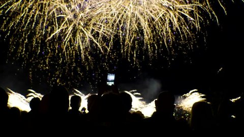 Szczecin, Poland - 12 05 2018: A crowd of people watch a beautiful fireworks display while some record on their phones (slow motion).