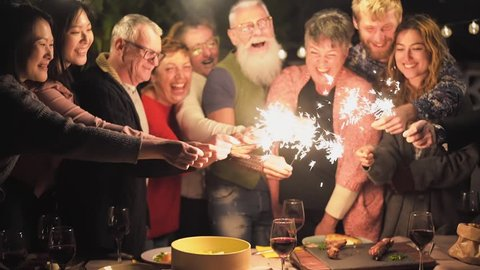 Happy family and friends celebrating with sparkler fireworks after dinner - Different age of people having fun drinking wine at birthday bbq party outdoor - Celebration concept - Focus on hands