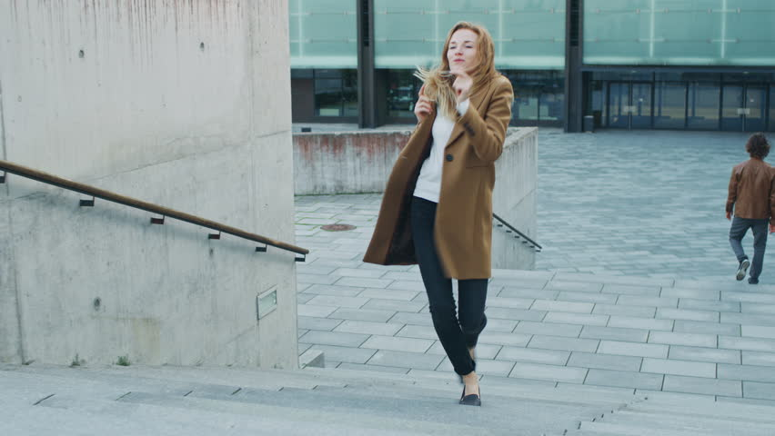 Cheerful and Happy Young Woman Actively Dancing While Walking Up the Stairs. She's Wearing a Long Brown Coat. Scene Shot in an Urban Concrete Park Next to Business Center. Day is Bright.