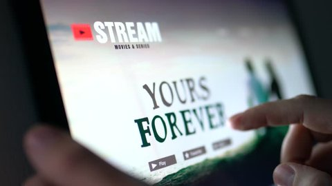 Movie stream service online. Man choosing series or film with tablet and touch screen. Streaming on demand video or watching an episode of a tv show with mobile device. All content is made up.