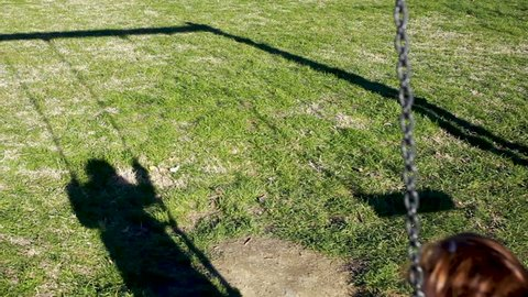Toddler girl plays on the swing. Science concept, example of shadow, energy, inertia and gravity.