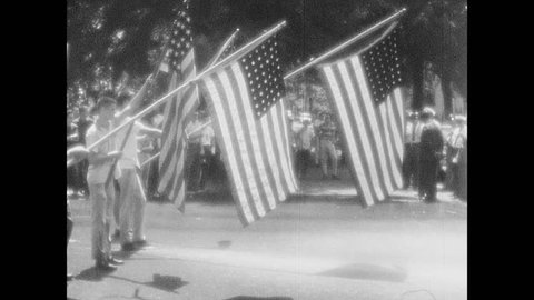 1950s: UNITED STATES Protesters hold flags. Police stand with firemen spraying hoses. Teenage boy pretends to swim on wet street.