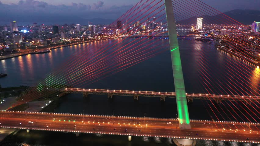 Aerial top view Tran Thi Ly Bridge, Han river in Da Nang City, Vietnam Da Nang city at sunset which is one of the most beautiful place of Vietnam for tourists. | Shutterstock HD Video #1024439108