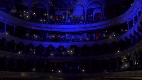 Hall of the Opera House with people with lights on, luminous telephones