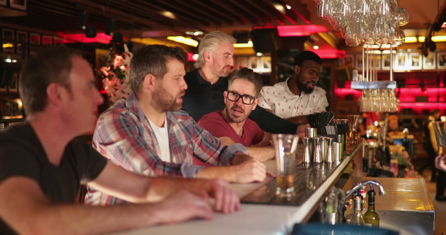 Small group of mid adult male friends sitting at a bar counter. They're trying a sample of beer and laughing together. | Shutterstock HD Video #1024468088