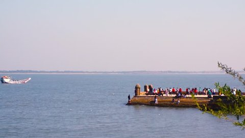Diu, Gujarat, India - Circa 2018 : People walking on the stone jetty stretching out in the arabian sea towards pani kotha Diu beach gujarat india. This structure is a famous landmark and a very very