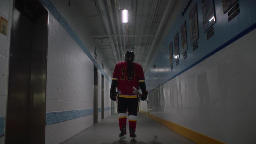 Hockey player walks from dressing room down long corridor hallway in hockey arena. Filmed with Arri Alexa Mini