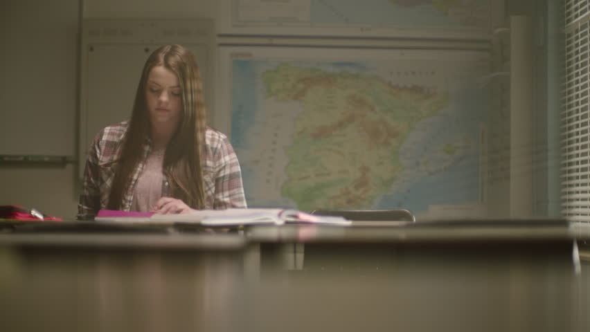 Female student in classroom surrounded by textbooks writes in her notebook working on school work in a classroom setting with map behind her and desks in the foreground. Filmed with Arri Alexa Mini | Shutterstock HD Video #1024494818