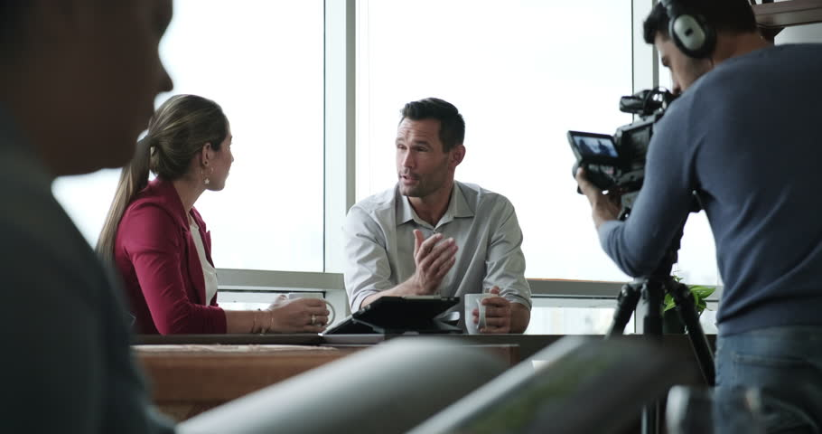 Happy businessman during corporate interview with female journalist. Manager answering question in office. Young woman at work as reporter with business man and filmmaker recording with video camera | Shutterstock HD Video #1024511918