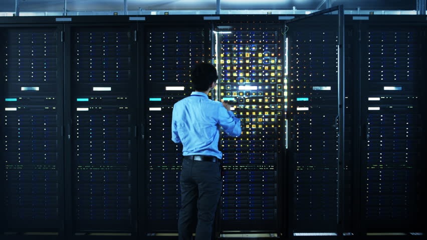 The Concept of Digitalization of Information: IT Specialist Standing In front of Server Racks with Laptop, He Activates Data Center with a Touch Gesture. Animated Visualization of Network Data | Shutterstock HD Video #1024515128