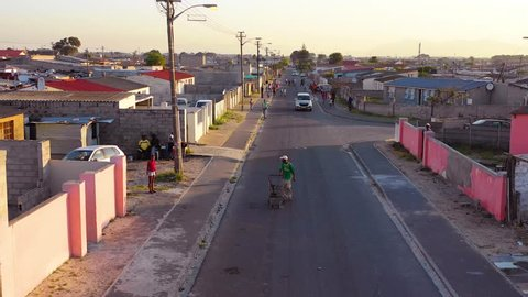 GUGULETHU, SOUTH AFRICA - CIRCA 2018 - Aerial over street scene in township of South Africa, with man and shopping cart walking on streets.