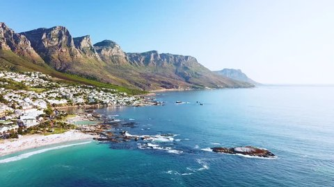 CAPE TOWN, SOUTH AFRICA - CIRCA 2018 - Aerial moving along the shoreline of Camps Bay, Cape Town, South Africa, with Twelve Apostles mountains.