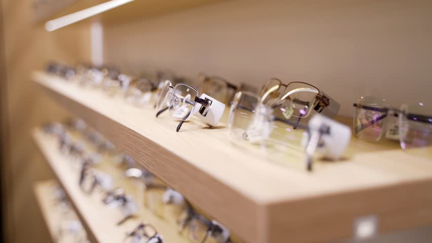 Glasses for sight. Sunglasses in a store. A collection of frames on the store shelf. | Shutterstock HD Video #1024568318