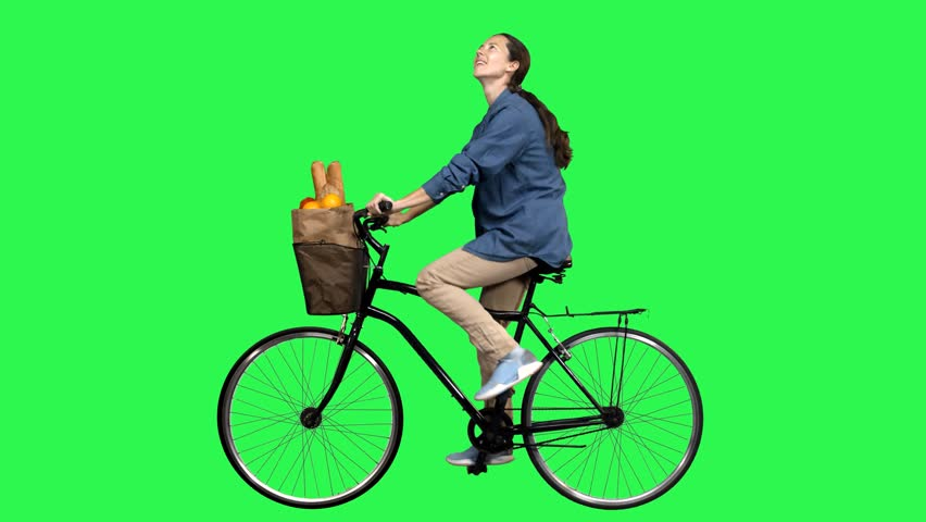 Happy woman riding a bicycle over a green screen, looking around, waving hello. No motion blur for optimal keying.