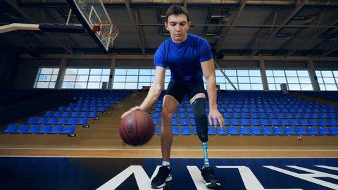 Nizhny Novgorod, Russia - CIRCA November 2018: Male athlete with a bionic leg is doing a basketball exercise