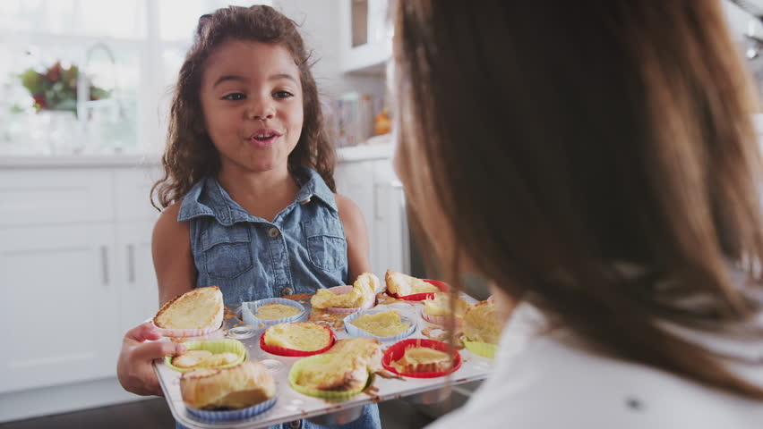 Happy young girl walks into focus and presents the cakes she?s made to her mum, over shoulder view | Shutterstock HD Video #1024666988