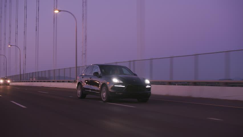 Portland, OR / USA Circa 2018 - Tracking shot of Porsche SUV driving on freeway bridge at dusk.