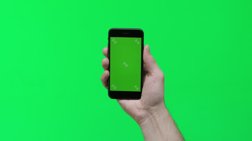 Male hand holding smart device on green screen chroma background making gestures, zoom in, pinch, swipe, scroll | Shutterstock HD Video #1024737698