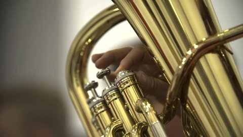 Musical Tuba instrument being played by pressing the valves in a orchestra concert indoors (close up shot) (slow motion shot)
