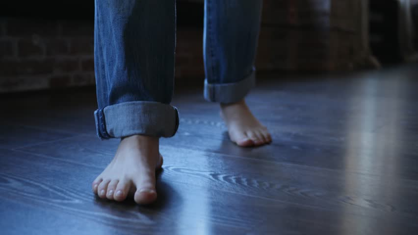 Barefoot girl legs in jeans trousers walking on parquet floor at home | Shutterstock HD Video #1024762868