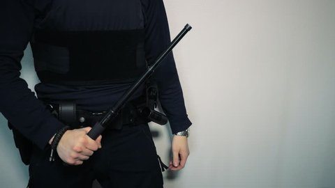 Police officer pulls out telescopic expandable baton, puts it back in holster