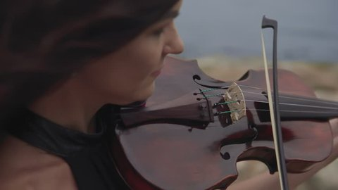 Young violinist in long black dress plays with inspiration at sea background. Beautiful girl with violin. Close up of violin. Art concept in 4k