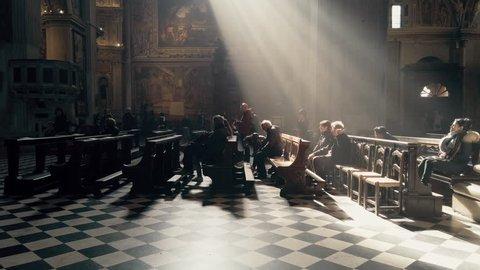 Bergamo, Italy - Feb, 2019: Rays of light illuminate a moment of prayer in the Basilica of Santa Maria Maggiore, Citta Alta, Bergamo, Italy.