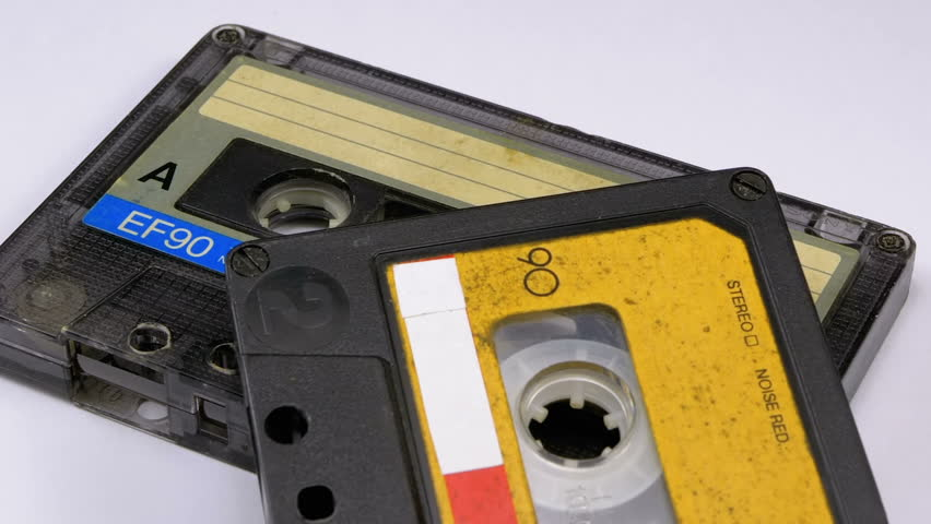 Two Audio Cassettes Rotates on White Background. Yellow and transparent with blue retro vintage tape cassettes with a blank label. Old music. Close-up. | Shutterstock HD Video #1024867808
