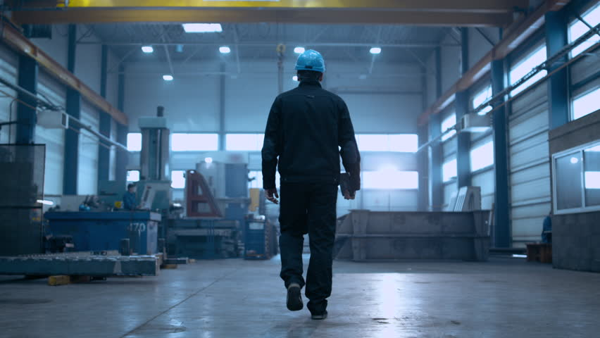 Following Shot of Professional Factory Worker Wearing Hard Hat Holds Tablet Computer, Walking Thorugh Modern Industrial Manufacturing Facility