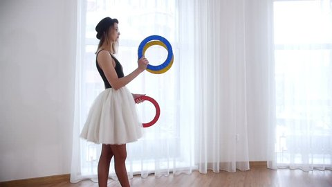 Young woman ballerina juggling with circle things