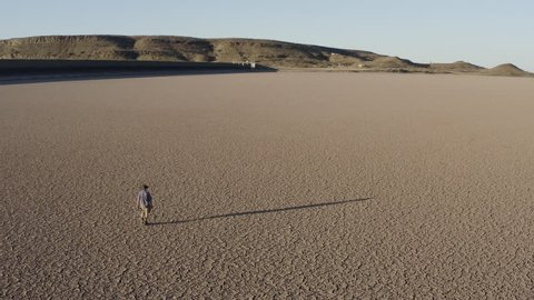 4K aerial view of a devastated farmer walking across a dry dam due to drought from climate change and global warming