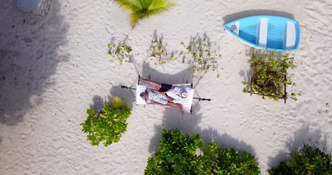 Descending from a high aerial perspective toward a couple relaxing together in a hammock on a white tropical beach in the Bahamas. Aerial,lookdown,descent,4k.