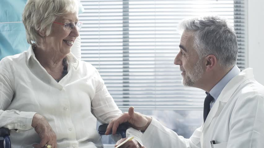 Professional doctor and nurse talking to a smiling senior female patient on a wheelchair and comforting her, the geriatrician is holding her hands | Shutterstock HD Video #1024918448
