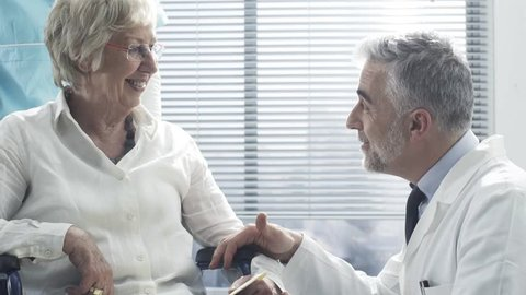 Professional doctor and nurse talking to a smiling senior female patient on a wheelchair and comforting her, the geriatrician is holding her hands