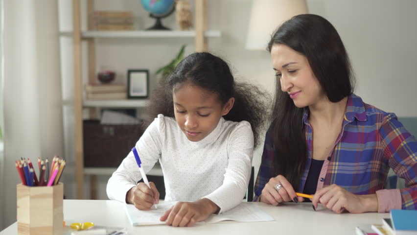 African happy smillimg student in school learning new knowledge doing exercise in notebook with the helping and assistance of an adult teacher. African american girl sitting in flat with her mother | Shutterstock HD Video #1024988288